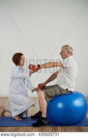 Physical Therapist Asking Senior Man Sitting On Fitness Ball To Lift Hand With Dumbbell, Rehabilitat