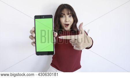 Wow And Shock Asian Beautiful Girl Point On Green Screen Phone With Blurry Background On Face In Whi