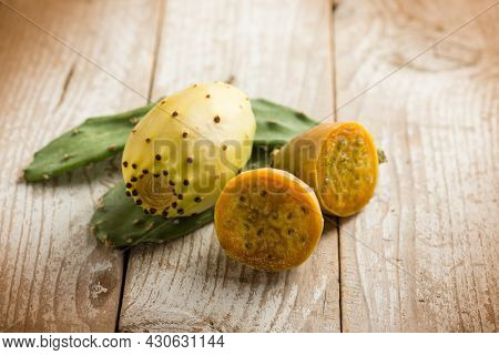 prickly pears and leaves over wooden background