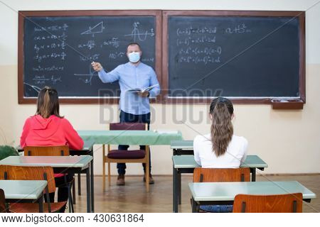 Teacher and his students wearing protective face mask in the classroom. Social distanting and classroom safety during coronavirus epidemic