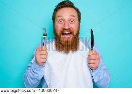 Hungry Man With Tattoos Is Ready To Eat With Cutlery In Hand