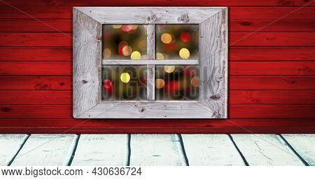 Image of flickering christmas fairy lights seen through window with red walls in the background. christmas festivity celebration concept digitally generated image.