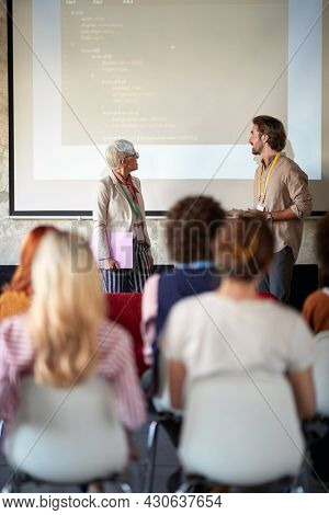 young caucasian male giving presentation to a group of people with his elderly female supervisor. teaching and learning concept.