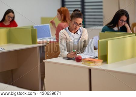 A female student reading a new lesson at the lecture in the university classroom. Smart young people study at the college. Education, college, university, learning and people concept