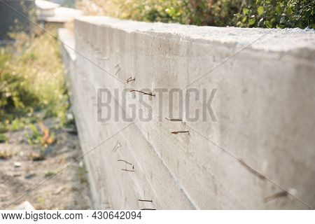 Retaining Concrete Wall. Side View. Reinforcement Elements Protrude From The Concrete. Retaining Wal