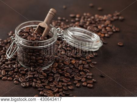 Roasted Coffee Beans In Glass Jar With Wooden Scoop On Brown Background. Macro