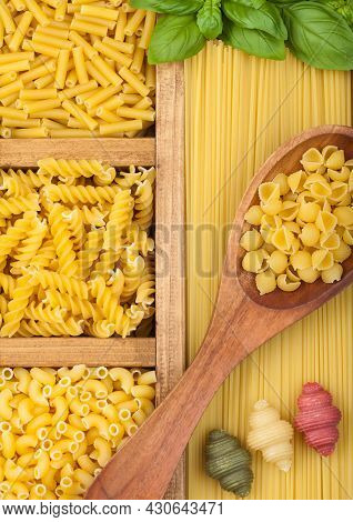 Box With Spaghetti And Fusilli And Macaroni With Maccheroni And Fresh Basil With Wooden Spoon And Tr