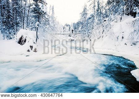 Stunning landscape of hanging bridge over river in snow covered forest in Oulanka National Park in Lapland Finland