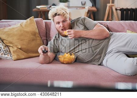 Lazy Overweight Man Lying On The Sofa Eating Chips And Watching Tv At Home