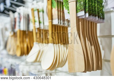 Shop Window With Wooden Kitchen Utensils. Sales Of Household Goods. Cooking Spatulas Hang In Row.
