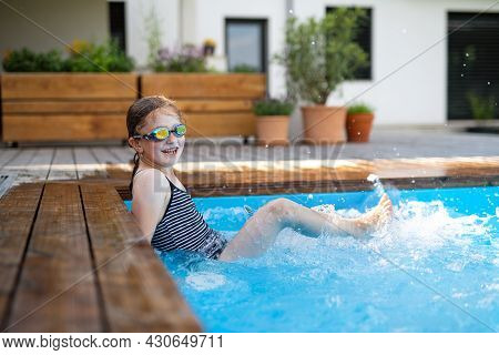 Small Girl With Goggles Outdoors In The Backyard, Sitting In Swimming Pool And Looking At Camera.