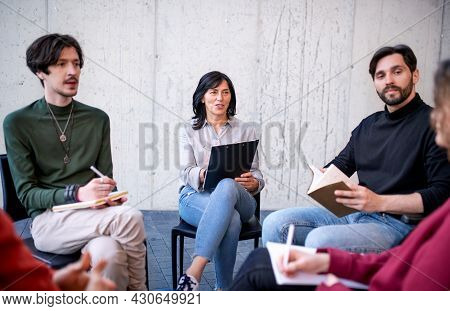 Counselor With Men And Women Sitting In Circle During Group Therapy, Talking.