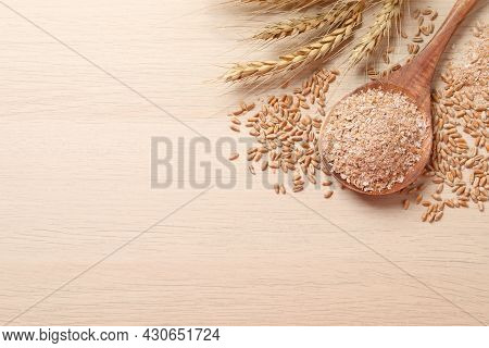 Wheat Bran, Kernels And Spikelets On Wooden Table, Flat Lay. Space For Text
