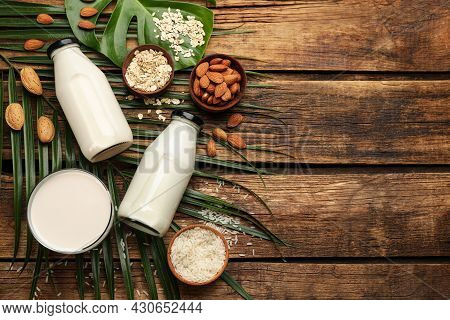 Different Vegan Milks And Ingredients On Wooden Table, Flat Lay. Space For Text