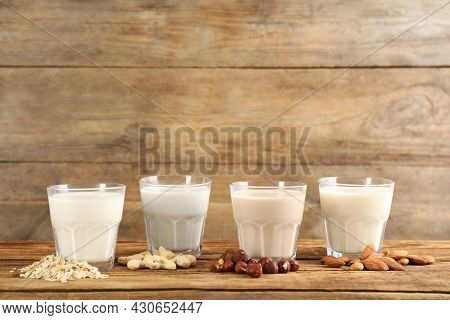 Different Vegan Milks And Ingredients On Wooden Table. Space For Text