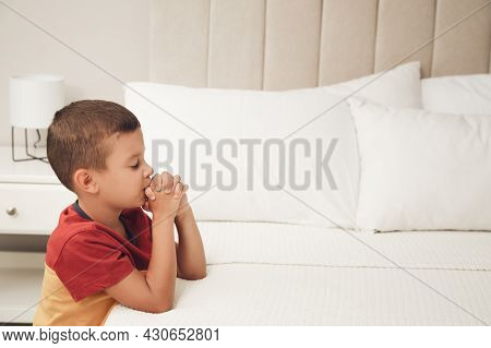 Cute Little Boy With Hands Clasped Together Saying Bedtime Prayer At Home. Space For Text