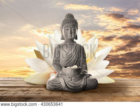 Beautiful Stone Buddha Sculpture With Flower Petals On Wooden Surface At Sunset