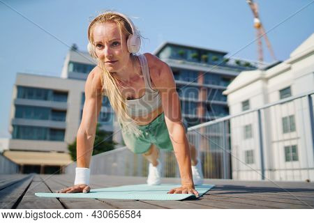 Mid Adult Woman Doing Push-ups Outdoors In City, Exercise And Healthy Lifestyle Concept.