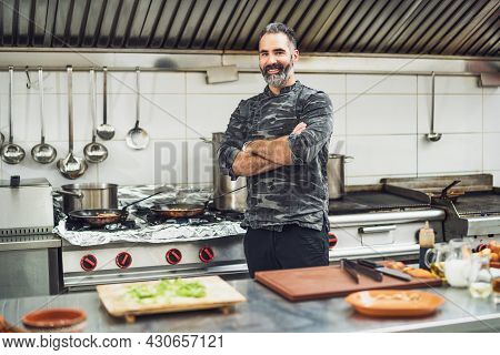 Professional Cook Is Ready For Preparing Meal In Restaurant's Kitchen.