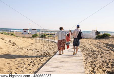 Photo From Behind Of Happy Young Family Of Three, Walking Towards Summer Sea Beach Along Wooden Path