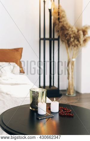 Cropped Photo Of Cozy Bedroom Interior. Round Table With Burning Candles, Slowly Smoldering Incense