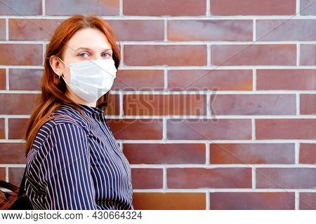 Red-haired Woman With Red Sore Eyes In A Protective Mask At The Brick Wall, Copy Space For The Inscr