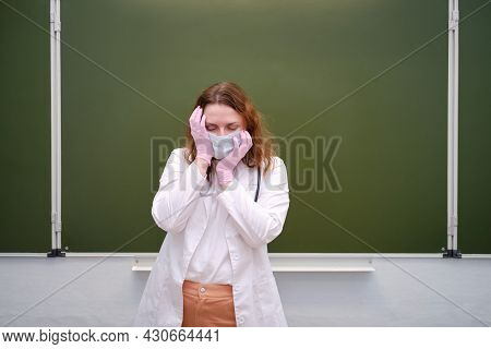 Weary Doctor In Face Mask In School Classroom, Copy Space. School Education During The Coronavirus E