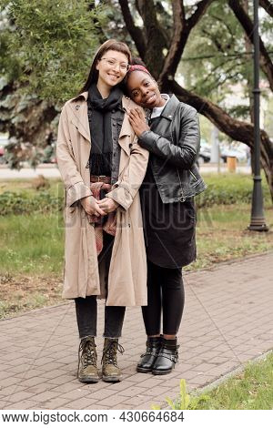 Two young affectionate females in casualwear standing on road in public park