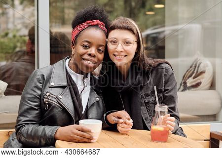 Young cheerful girlfriends in casualwear looking at you with toothy smiles in outdoor cafe