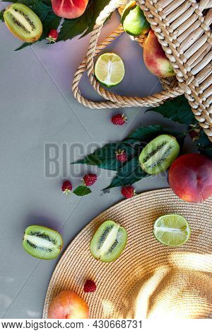 Flat Lay Of Straw Hat And Bag With Fruits On Grey Background In Sunlight, Summer