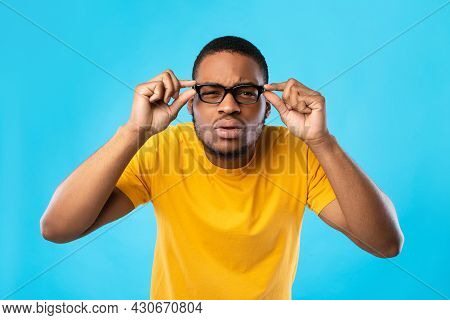 African American Guy With Poor Eyesight Squinting Eyes, Blue Background