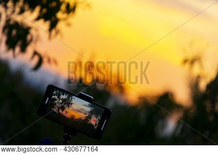 Photograph On A Mobile Phone While Recording A Sunset Time Lapse With A Sun Over The Sky Of Madrid,