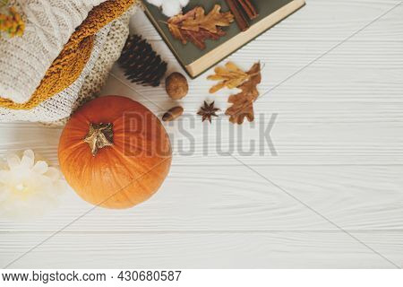 Autumn Flat Lay With Copy Space. Pumpkin, Cozy Sweaters, Autumn Leaves, Burning Candle And Vintage B