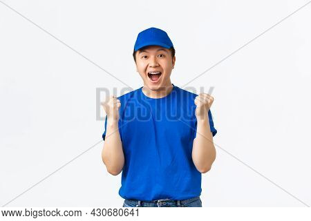 Excited And Happy Asian Courier In Blue Uniform Shouting Yes And Rejoicing, Fist Pump As Celebrating