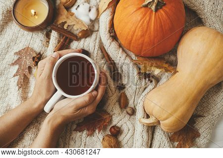 Hands Holding Warm Cup Of Tea On Stylish Cozy Sweater With Pumpkins, Autumn Leaves, Burning Candle.