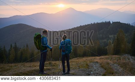 Rear View Of Lover Pair Of Hikers Standing On Mountain Trail And Leaning On Trekking Sticks Watching