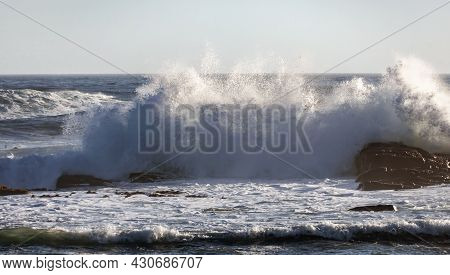 High Storm Wave With Foam And Spray Breaks On The Shore. Evening Storm On The Southern Sea Coast.