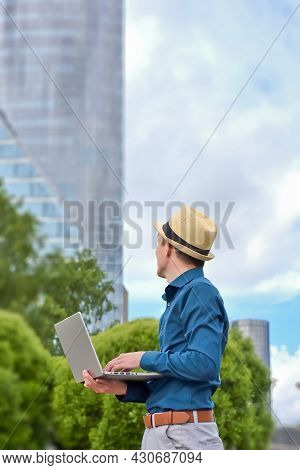 Young Man With A Laptop Works Remotely Outdoors And Looks Towards The Office Building. Work And Stud