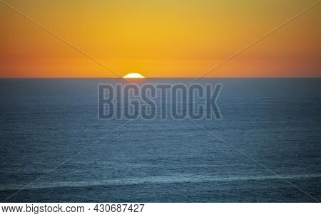 Evening Twilight And Sunset With The Horizon Line In The Ocean. Landscape With The Edge Of The Solar