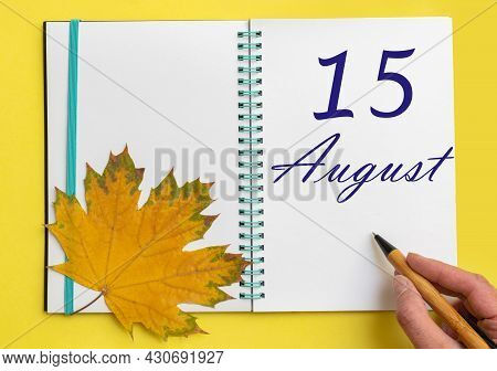 15th Day Of August. Hand Writing The Date 15 August In An Open Notebook With A Beautiful Natural Map