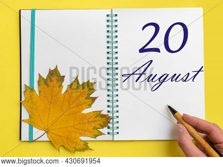 20th Day Of August. Hand Writing The Date 20 August In An Open Notebook With A Beautiful Natural Map