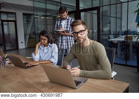 Young Caucasian Man, Male Office Worker Using Laptop, Sitting At Office Desk And Looking At Camera.