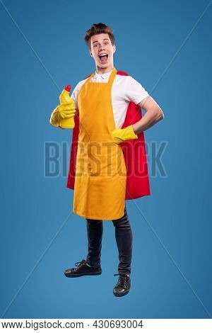Full Body Delighted Young Superhero With Bottle Of Detergent Holding Hand On Waist And Looking At Ca