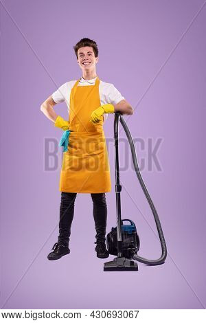 Proud Young Male In Yellow Apron And Gloves Standing Near Electric Vacuum Cleaner And Smiling Happil