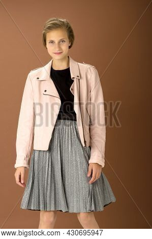 Happy Girl Whirling Against Brown Background. Joyful Attractive Brown Haired Teen Girl Dressed Pink