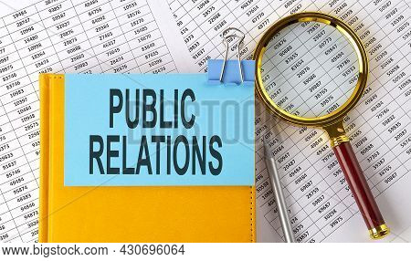 Public Relations Text On Sticker On Notebook With Magnifier And Chart. Business
