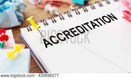 Accreditation - Text On A Notepad With Wrinkled Paper And Paper Needles On Wooden Background.