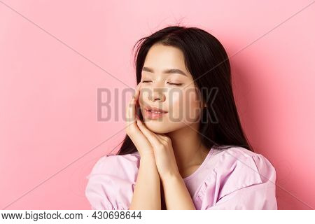 Tender And Romantic Girl Gently Touching Face, Close Eyes And Smiling Softly, Standing On Pink Backg