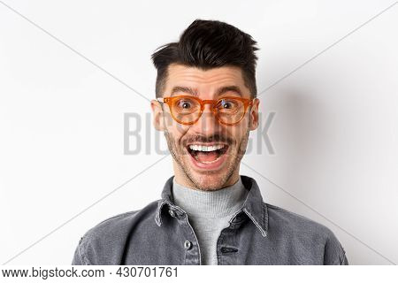 Excited Handsome Man In Trendy Eyewear Checking Out Awesome Promo, Smiling Amused, Standing Happy On