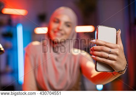 Smiling Arabian Woman In Hijab Taking Selfie On Cell Phone While Sitting At Table At Living Room. Fo